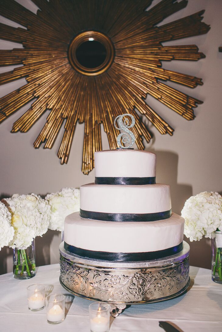 Christina and Neil kept their color palette in mind when they chose to serve a simple yet stunning three-tier white wedding cake with gray accents and a sparkly monogrammed cake topper.