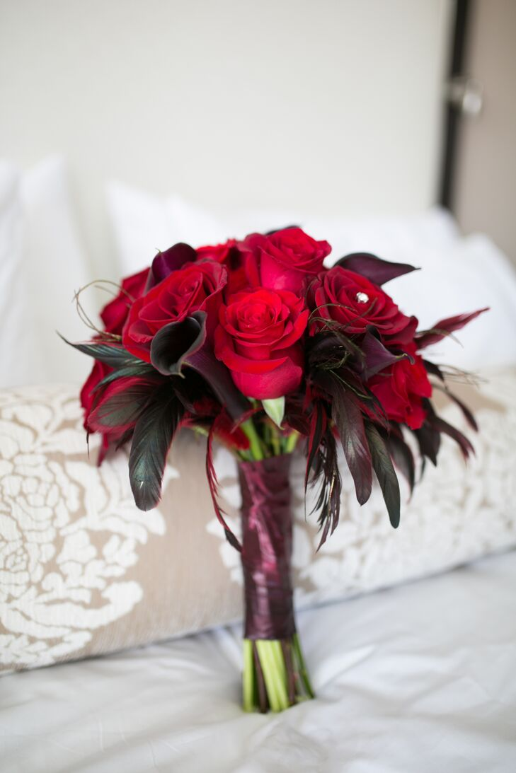 Nicole held a black-wrapped bouquet of red roses and calla lilies mixed in with red feathers because of her love for birds.