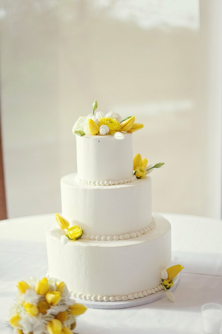 Clusters of fresh yellow tulips and roses popped on the simple white butter cream cake.