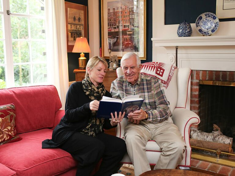 Couple sitting on sofa reading StoryWorth memoir