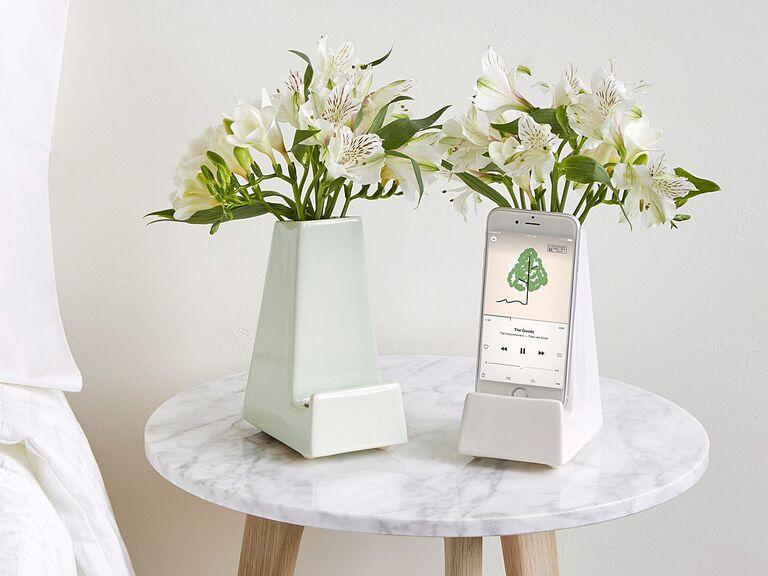 Mint and white smartphone holder vases on bedside table