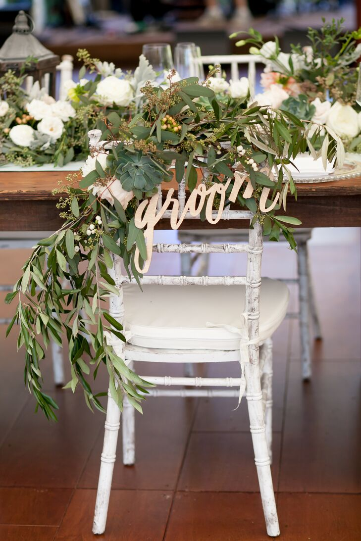Rebecca and James decided against a sweetheart table, but Dragonfly Events made sure their seats stood out: draped in cascading garlands of eucalyptus and whimsical bride and groom signs.