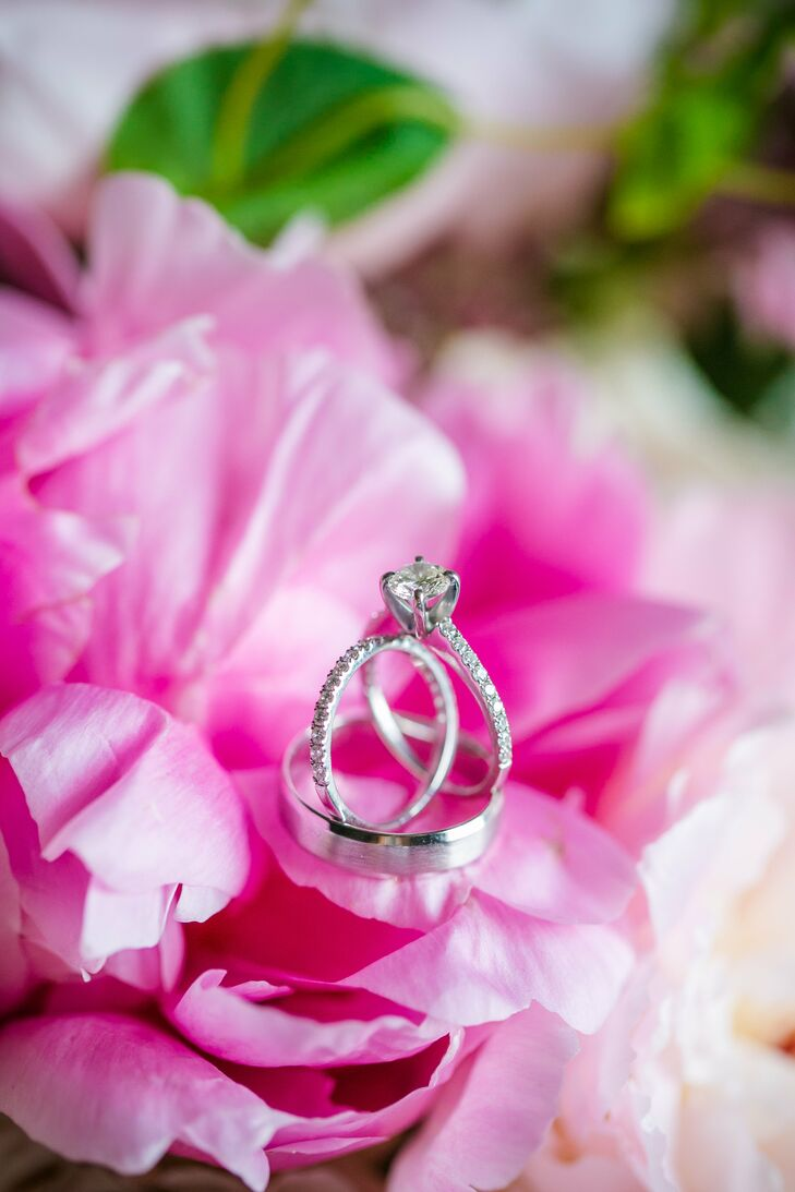 Callie's ring is a round-cut diamond with a delicate band containing smaller diamonds; the wedding band also contains smaller diamonds to match. Brian's ring is a simple white, gold-brushed band.