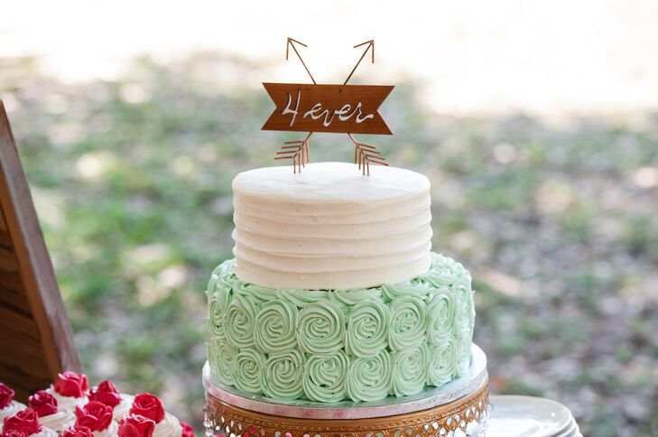 """For guests who weren't in the mood for the cookie bar, Sarah and Sean also had a two-tier buttercream cake topped with a rustic """"4 ever"""" sign. It was even surrounded by cupcakes that were accented with red rosettes."""