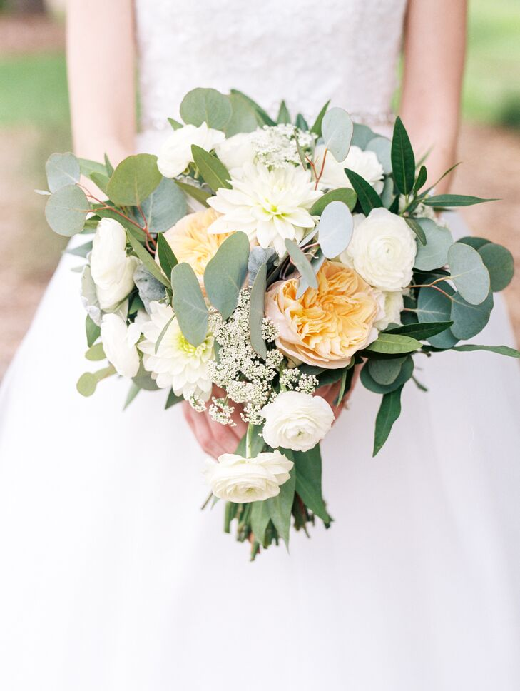 Nathalie's loose and natural bouquet displayed a muted color palette of eucalyptus greens with pops of peach garden roses, white ranunculus and dahlias, dusty miller, bay laurel and Queen Ann's lace wrapped in a thin band of ivory lace.