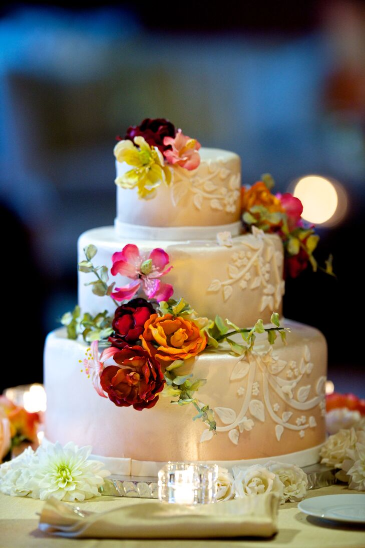 """One of the groom's cousins, Margaret Lastick, made the wedding cake. """"We showed her pictures of our floral arrangements, and she made the most beautiful cake to match,"""" says Brielle. The champagne exterior mirrored the table linens, and the sugar blossoms reflected the vibrant summer color palette."""