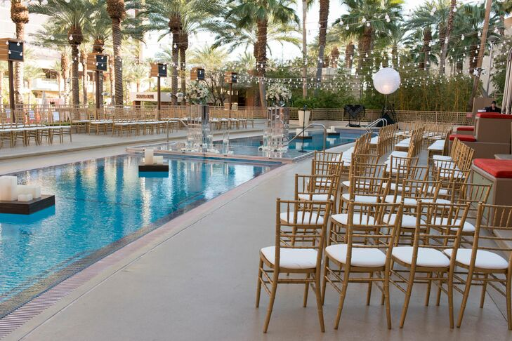 Gold chiavari chairs were placed next to the pool, where a clear platform was set up over it. The same chairs were later used as seating for the dinner with the tables placed around the pool.