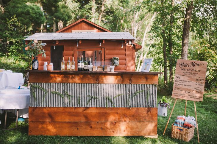 "At the backyard bar—created out of  reclaimed materials from a Minnesota farm—guests could order a signature Mitchell Lake Sunrise cocktail, a tap beer from local Bent Brewstillery or Able Seedhouse & Brewery, and listen to a classic rock playlist. The cocktail hour ""felt like a relaxing summer day on the boat,"" Danielle says."