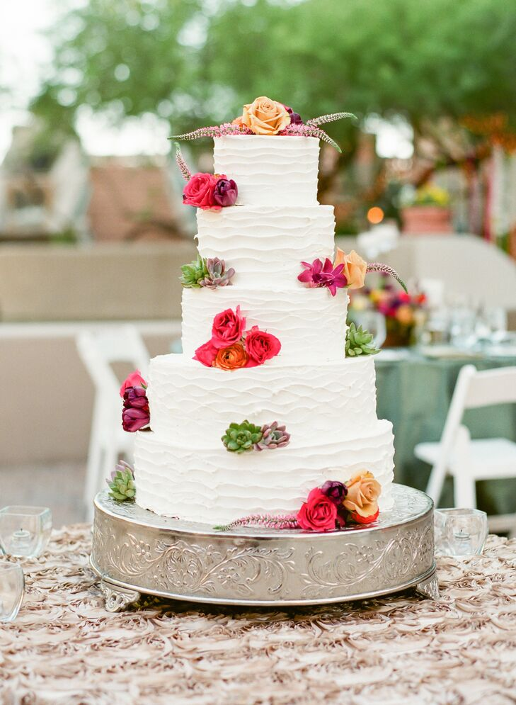 A simple, white tiered cake was transformed to with bold florals.