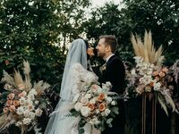 Bride and groom posing for wedding portrait in front of bohemian floral arrangement