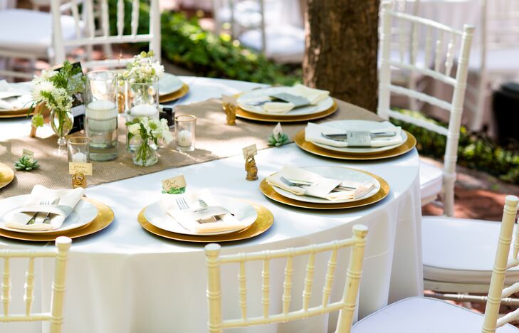 White linen tablecloths with burlap runners were set with ivory plates on gold chargers.