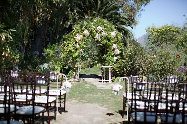 The ceremony was held outside beneath an arch overflowing with pink and white flowers and lots of lush greenery.