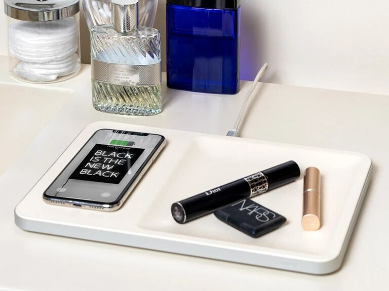 White trinket and wireless charging tray with phone and makeup on it