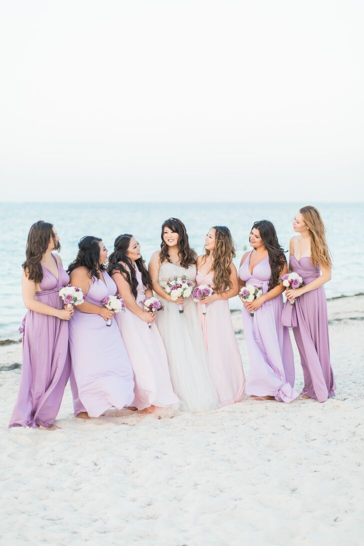 To create a cohesive yet customized look, Victoria had her bridesmaids don ethereal floor-length gowns in soft shades of lavender, blush and purple. The convertible style allowed the women to choose the look that suited them best. They wore their hair down in soft, romantic waves to channel a beach chic aesthetic.