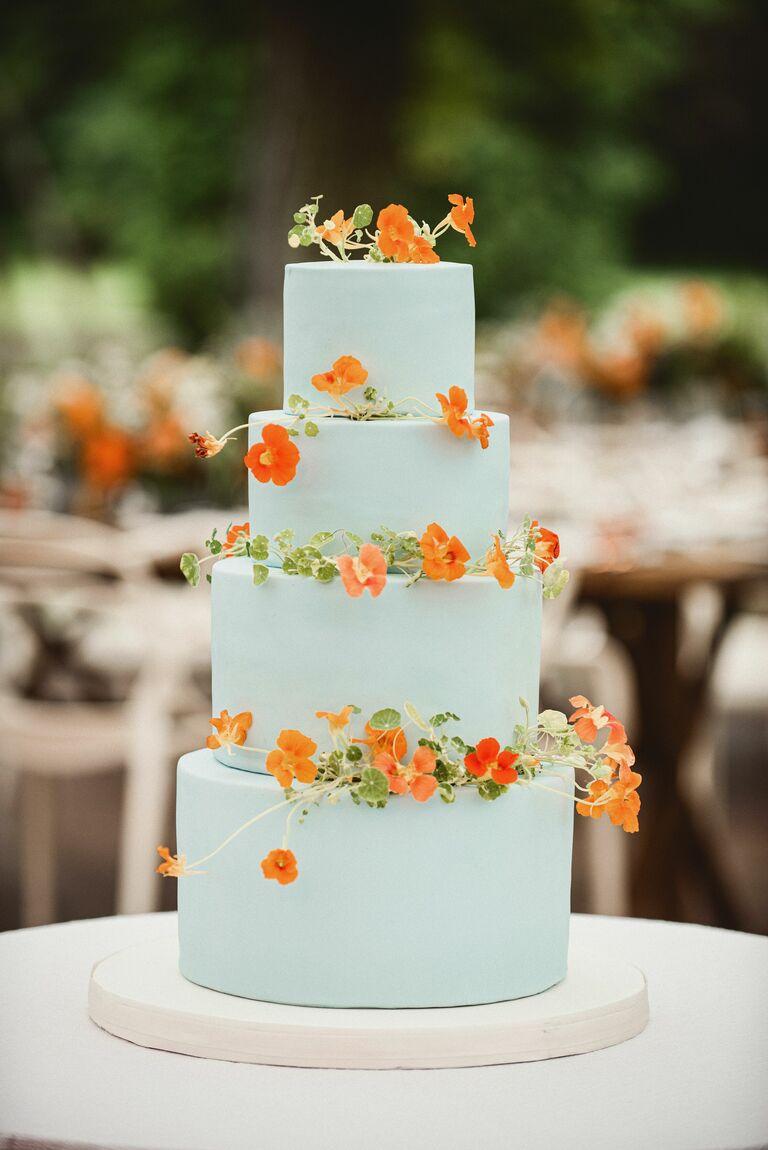 light blue wedding cake decorated with orange nasturtium flowers edible flowers that match 2021 wedding colors