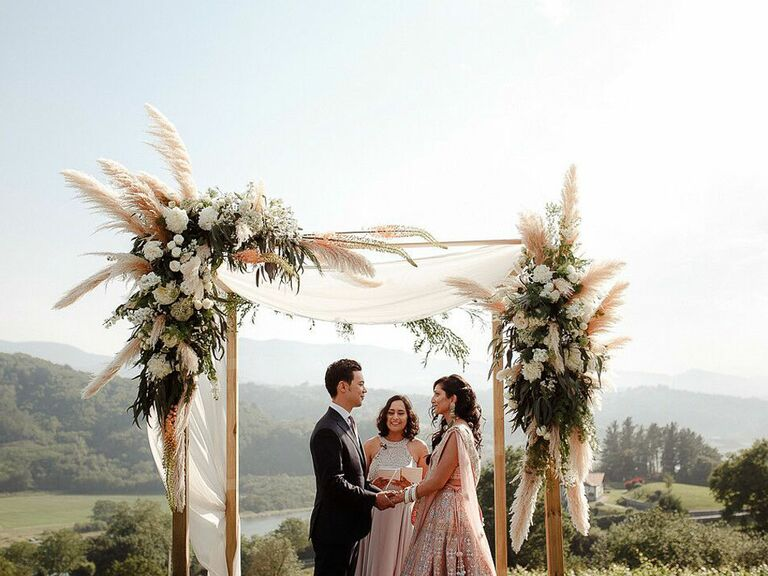 Couple exchanging vows in front of boho floral arch at outdoor summer wedding