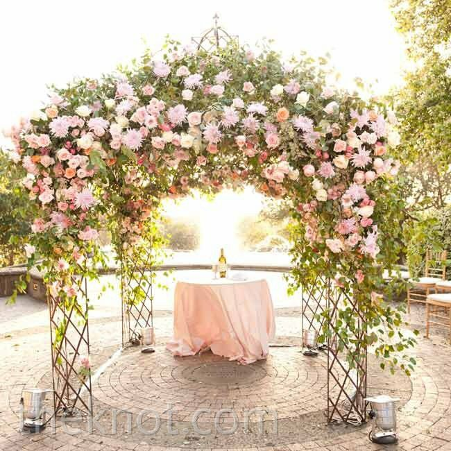 A huppah wrapped in pink flowers and branches made a stunning focal point for the outdoor ceremony.