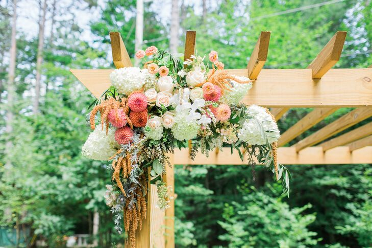 A cascading arrangement of playful pink dahlias, romantic roses, fluffy white hydrangeas and an assortment of textured vines was draped along the top of a wooden arbor, where Chrissy and Mike exchanged vows, adding a pop of vibrant color to the wooden green landscape.