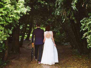 Bride and groom walking through forest