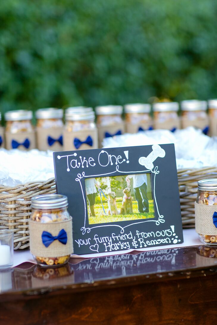 """Guest went home with sweet treats for themselves and their dogs. For the humans, Lauren and her mother made dozens of DIY mason jar favors filled with her grandmother's Chex Mix-inspired treats. """"They were a huge hit and people were taking several jars on their way out,"""" Lauren says. Of course, they couldn't forget about their furry friends, so Lauren and Andy also gave out doggie treats as favors."""