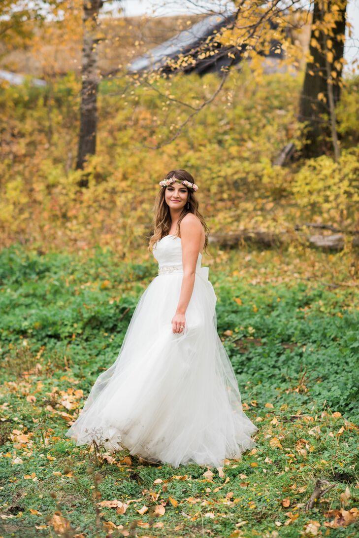"""While heading to the bridal salon is the first instinct for most brides-to-be, Julia tapped into her savviness and scored a stunning gown online. """"I found my dress on a used wedding dress website after seeing it in a store. I saved a lot of money buying it online, which allowed me to make alterations to lower the back of the dress,"""" she says. The Theia gown featured a strapless bodice that flowed into an ethereal skirt that swished with every step. She completed her look with a flower crown and gold flats to match the bridesmaid attire."""