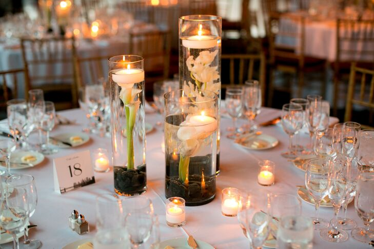 Hurricane vases filled with black river stones, ivory calla lilies and orchids and floating candles added a modern, romantic touch to each of the reception tables.