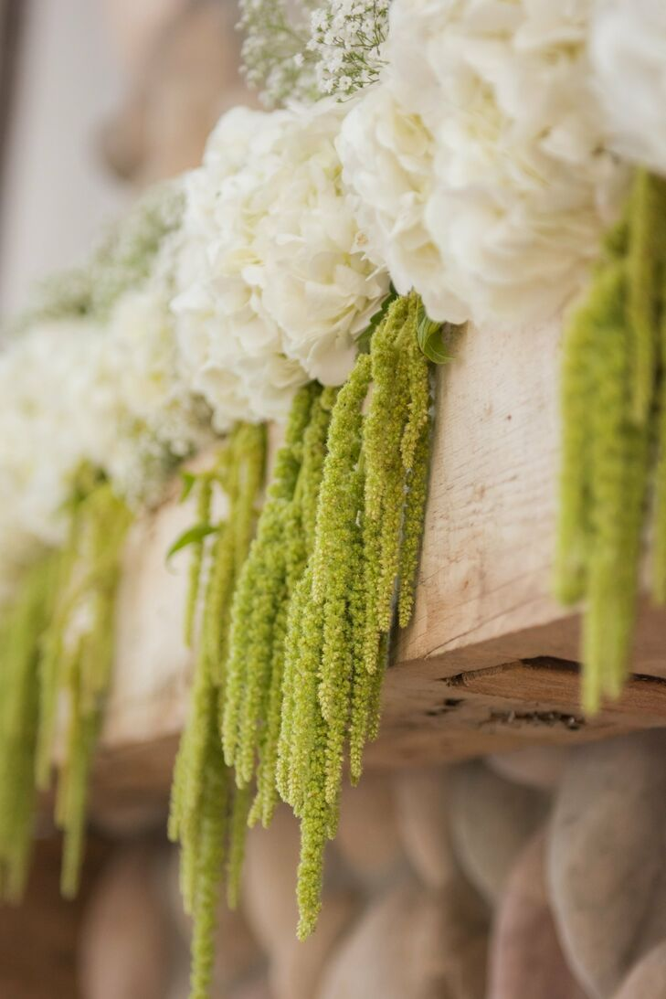 The stone fireplace in the Boathouse Chapel was decorated with hanging moss and bunches of ivory hydrangeas.