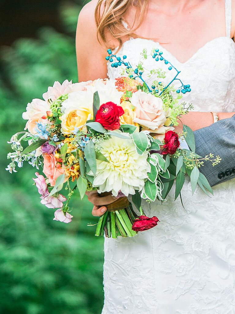 Bright wedding bouquet with roses, ranunculus, dahlias, seeded eucalyptus and tweedia