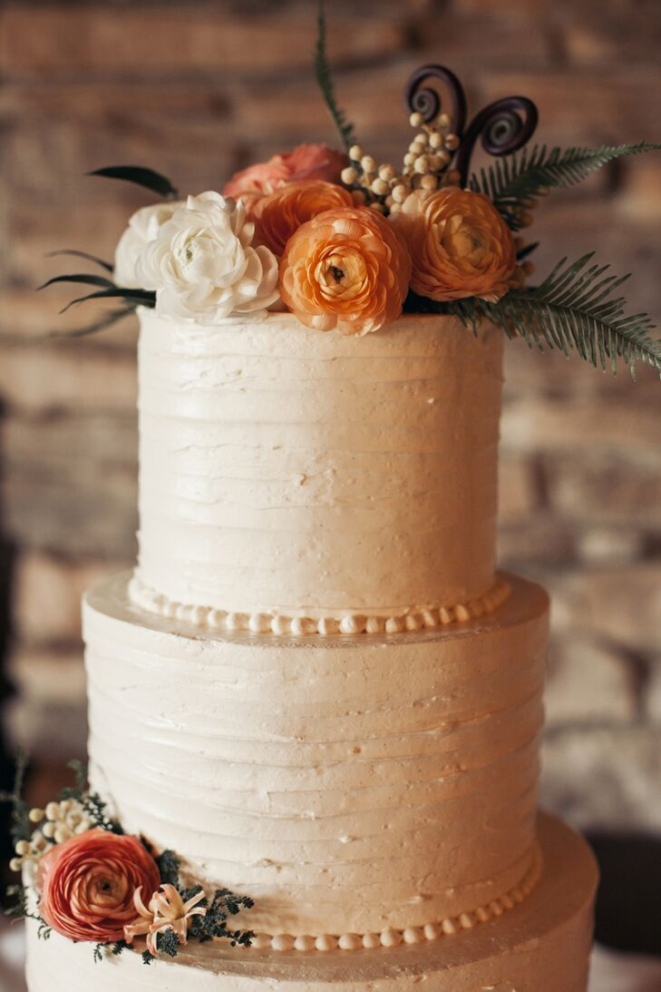 Covered in lightly textured champagne buttercream, the wedding cake by Love Birds Sweets matched the organic style of the wedding. Ranunculus in shades of ivory, orange and coral with sprigs of green completed the fresh, natural look.