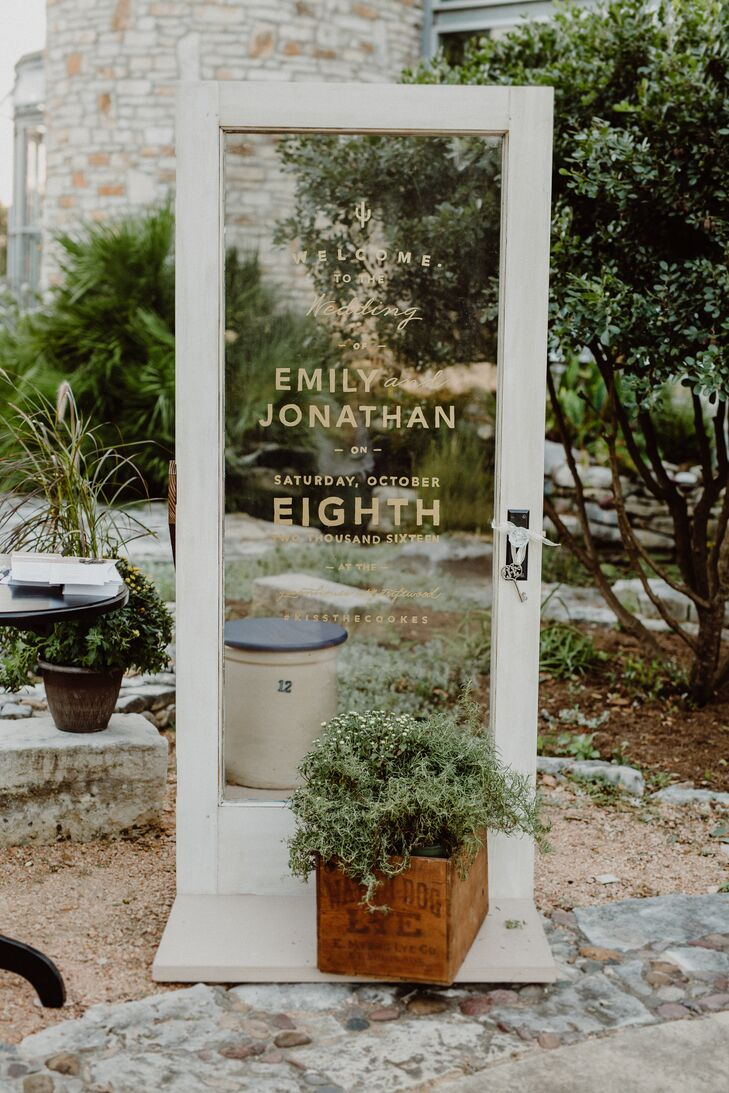 A clear glass door printed with Emily and Jonathan's names welcomed guests to the outdoor ceremony at the Greenhouse at Driftwood in Driftwood, Texas.