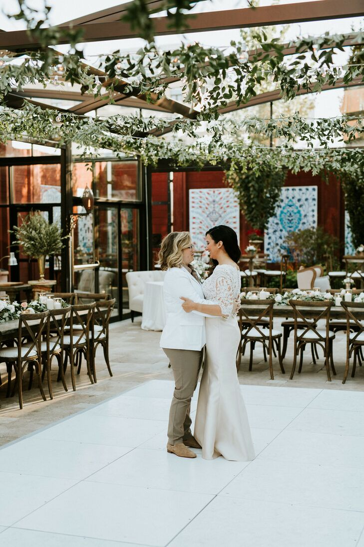 Couple on White Dance Floor with Hanging Greenery and String Lights Overhead