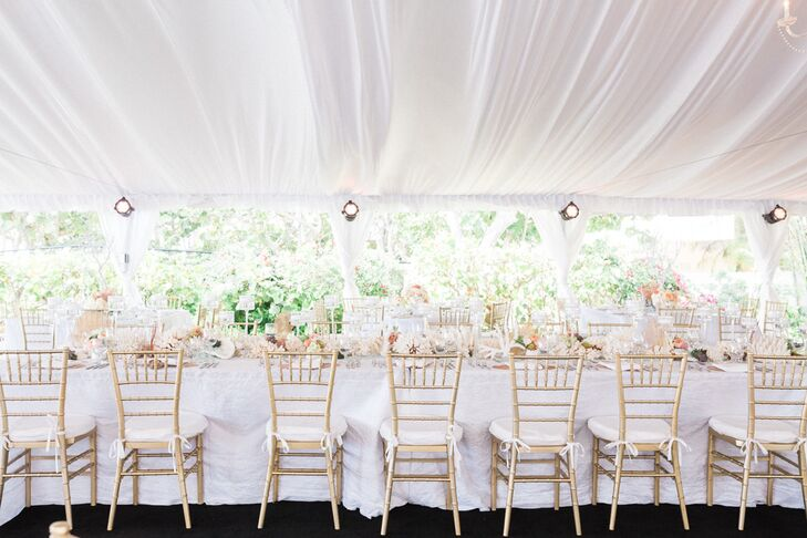 To offset the classic white and neutral decor throughout their tented reception, Stephanie and Dallas chose a few metallic accents. We love that they went with gold and ivory chiavari chairs for a subtle yet chic contrast.