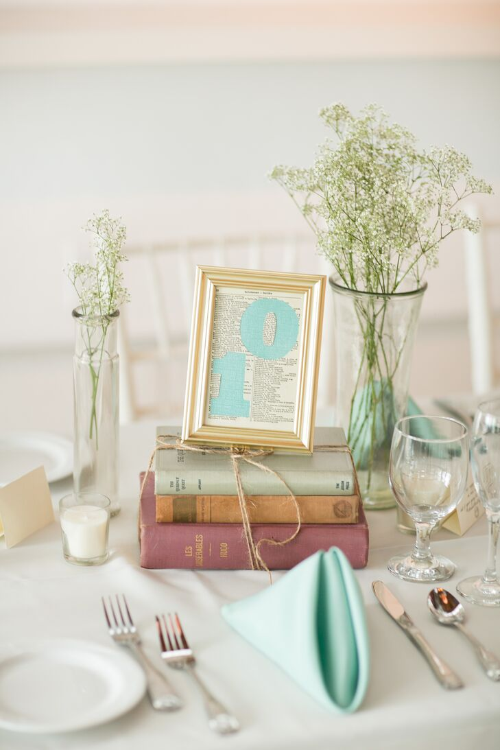 Julie collected vintage finds in the months before the big day. Framed table numbers on vintage book pages sat atop the stacks, while Baby's Breath filled the glass vases.