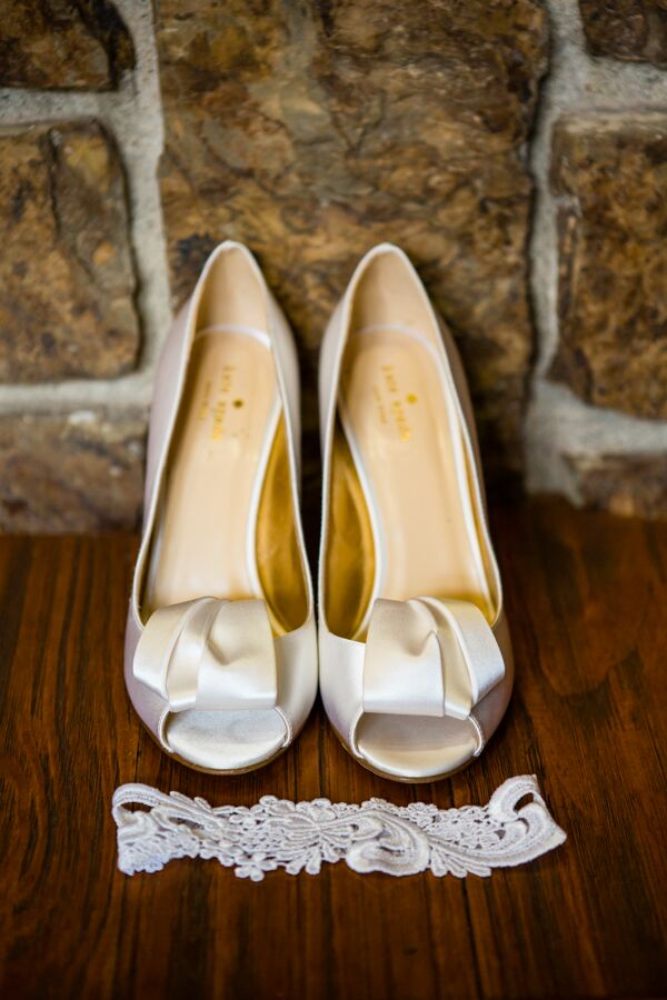 Michelle picked out a pair of ivory silk Kate Spade shoes with a peep toe and gorgeous ribbon design on top. Her white lace garter laid in front of the shoes, both going along with her white Monique Lhuillier dress.