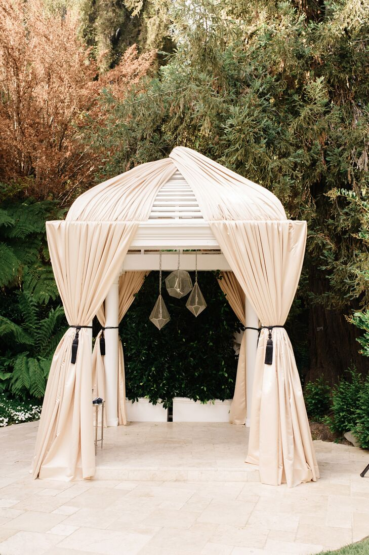 The couple draped champagne-colored fabric on the hotel's existing arbor structure as their huppah.