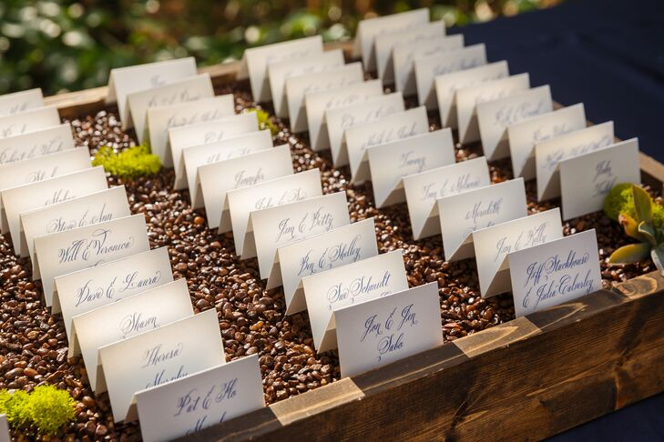 A wooden box filled with brown pebbles displayed rows of white escort cards, with guest names and table numbers written in navy blue script.