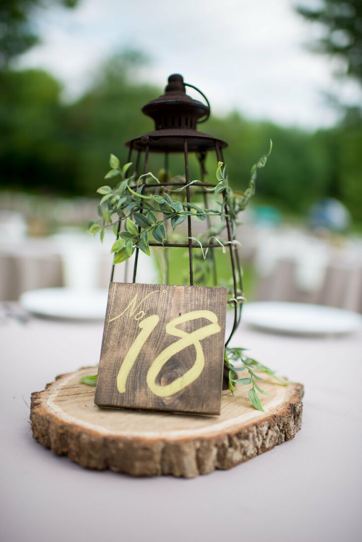 Some of the rustic centerpieces were black lanterns covered in greens and displayed on wooden slabs. Table numbers were written in gold on wooden blocks.