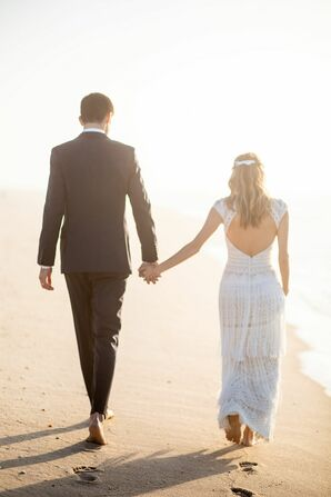 Couple Holding Hands as They Walk Along the Beach