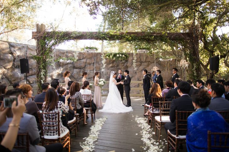 Woo Jin and Kyung exchanged vows outside amidst several hanging floral arrangements made with whit peonies, roses, and greenery like eucalyptus.