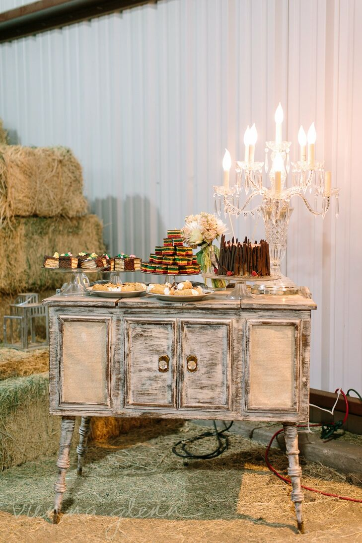 A distressed buffet table was piled high with a variety of desserts. An ornate candelabra added an elegant touch to the table, adding to the shabby-chic theme of the reception.