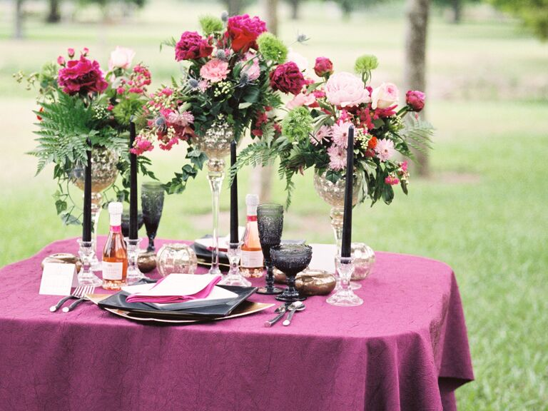 DIY centerpieces with bright pink roses, purple carnations and greenery