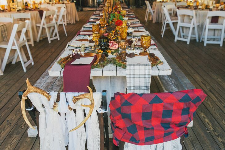 "The head table featured benches and special ""his and hers"" chairs for the bride and groom. Each featured antlers with strips of fabric that signified who sat where. The table had a moss runner with amber glass bottles filled with cattails, red peonies, ranunculus and lotus pods."