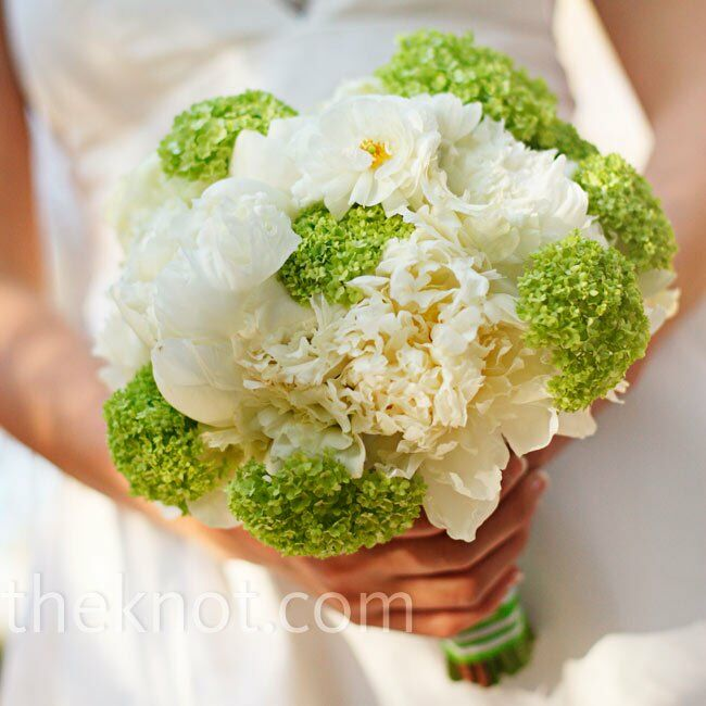 Green viburnum added a pop of color to this all-white clutch of peonies and ranunculus.