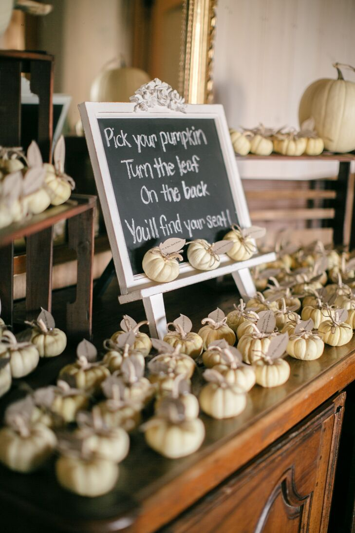 "Escort cards at this fall wedding were attached to seasonal mini white pumpkins as ""leaves."""
