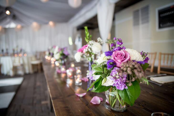 The couple decorated bare wood tables with a romantic mix of purple and clear vases. Each table had a different mix of flowers for an eclectic feel.