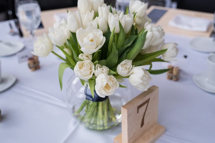 Clear bowls held the simple, elegant centerpiece arrangements of white tulips. The table numbers were engraved on blocks of wood.