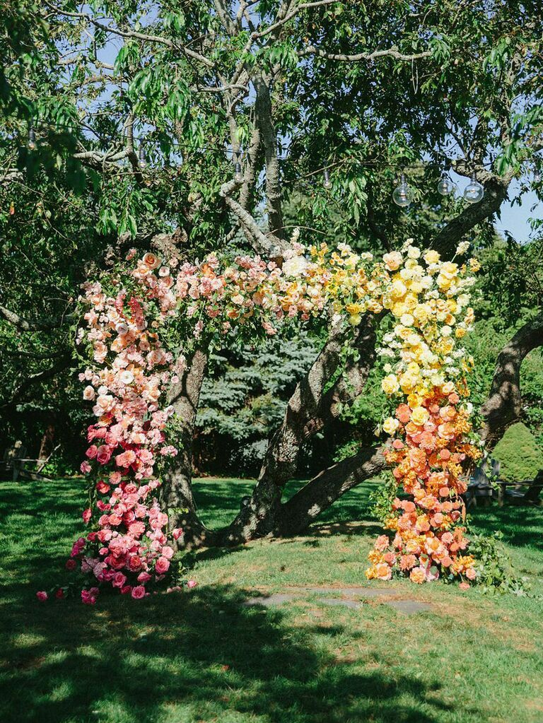 Pink ombré statement floral arch at outdoor summer wedding ceremony
