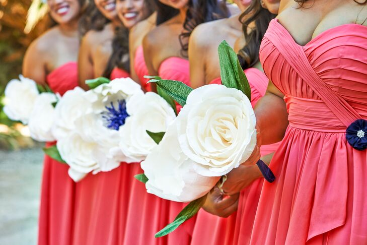 Bridesmaids wore strapless long dresses in coral, and held onto their ivory fabric rose bouquets.