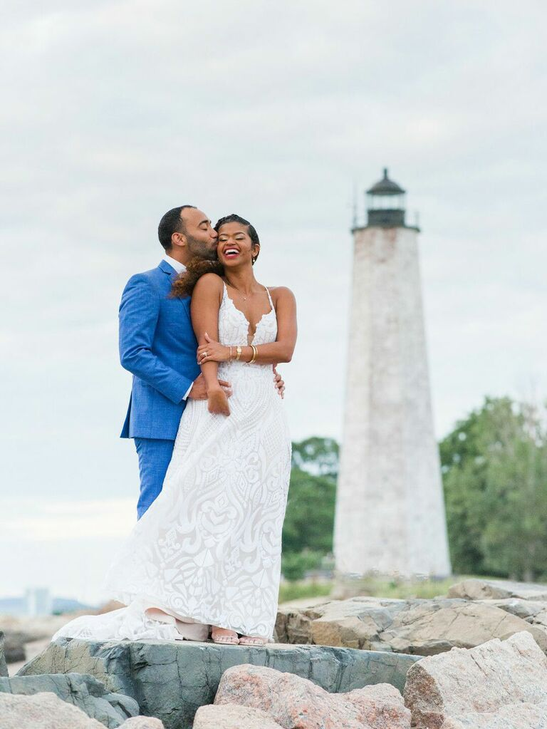 Bride and groom posing for portraits in front of lighthouse at nautical preppy summer wedding