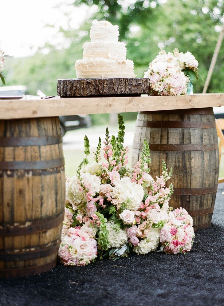 The newlyweds showed off their three-tier cake on a table made from vintage barrels.